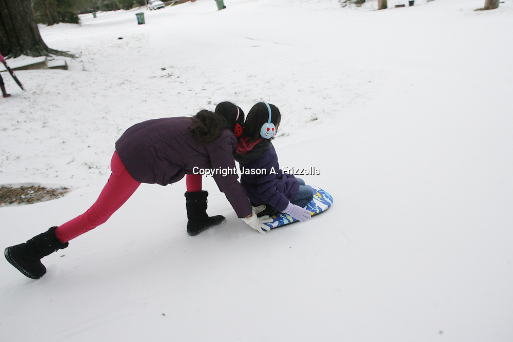 Flor Pena'- Medina, 16, left pushes her sister Jasmin Pena'-Medina, 9, on Larchmont Drive in Wilmington, N.C. Wednesday January 29, 2014. Wilmington saw a wintry mix of sleet, snow, and freezing rain Tuesday and Wednesday which caused extensive closings throughout the area. (Jason A. Frizzelle)