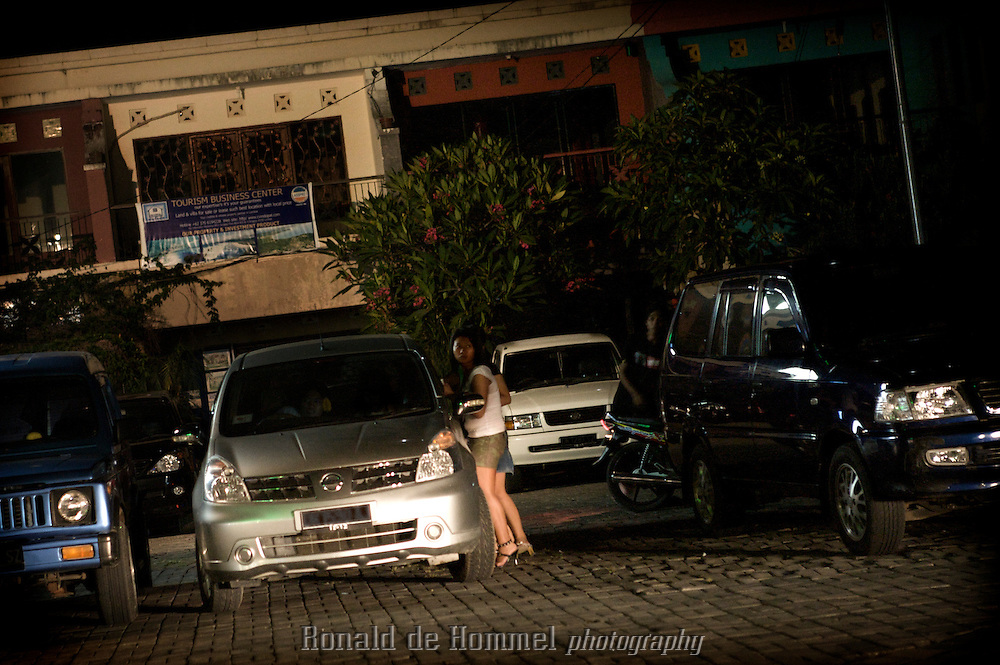 2009-03-07 Mataram, Indonesia. Two young girls in Mataram, Lombok chatting to a possible client are caught in the headlights af  an approaching car. .Child prostitution is a growing problem in Indonesia. Forced by poverty or lured by the luxury of modern life many girls end up in prostitution. Many girls make the first step just to be able to buy a mobile phone or to go out in an expensive nightclub. .Shopping malls are favorite hangouts to pick up clients. Schoolgirls skip classes and hang around, still in uniform, hoping for a client. Their pimps may be classmates of the same age. Regular customers keep in contact through SMS, Facebook of Friendster. Others hang out in nightclubs or on the street. Some clubs keep a few girls for their customers. They're kept as prisoners and are not allowed to leave the premises alone. ..Kakak a local women's organization in Java approaches girls and tries to educate them about their rights and offers them alternatives like vocational training. Terre des Hommes Netherlands is campaigning against child exploitation and supports Kakak..