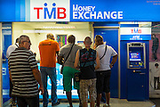 "24 AUGUST 2013 - BANGKOK, THAILAND: Tourists line up to buy Thai Baht at a money exchange booth in Bangkok. Thailand entered a ""technical"" recession this month after the economy shrank by 0.3% in the second quarter of the year. The 0.3% contraction in gross domestic product between April and June followed a previous fall of 1.7% during the first quarter of 2013. The contraction is being blamed on a drop in demand for exports, a drop in domestic demand and a loss of consumer confidence. At the same time, the value of the Thai Baht against the US Dollar has dropped significantly, from a high of about 28Baht to $1 in April to 32THB to 1USD in August.     PHOTO BY JACK KURTZ"