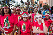 """10 OCTOBER 2010 - PHOENIX, AZ: Members of a Matachine group wait to start their performance in Phoenix Sunday. About 500 people processed through downtown Phoenix Sunday afternoon to honor the Virgin of Guadalupe, the """"Queen of the Americas."""" The procession was accompanied by 12 Matachine dance troupes. The Matachines are an important part of Mexican Catholic culture. They represent the battle of Good vs. Evil and the protect the Virgin from malevolent forces, represented by the demon like figures who accompany the dancers.      Photo by Jack Kurtz"""