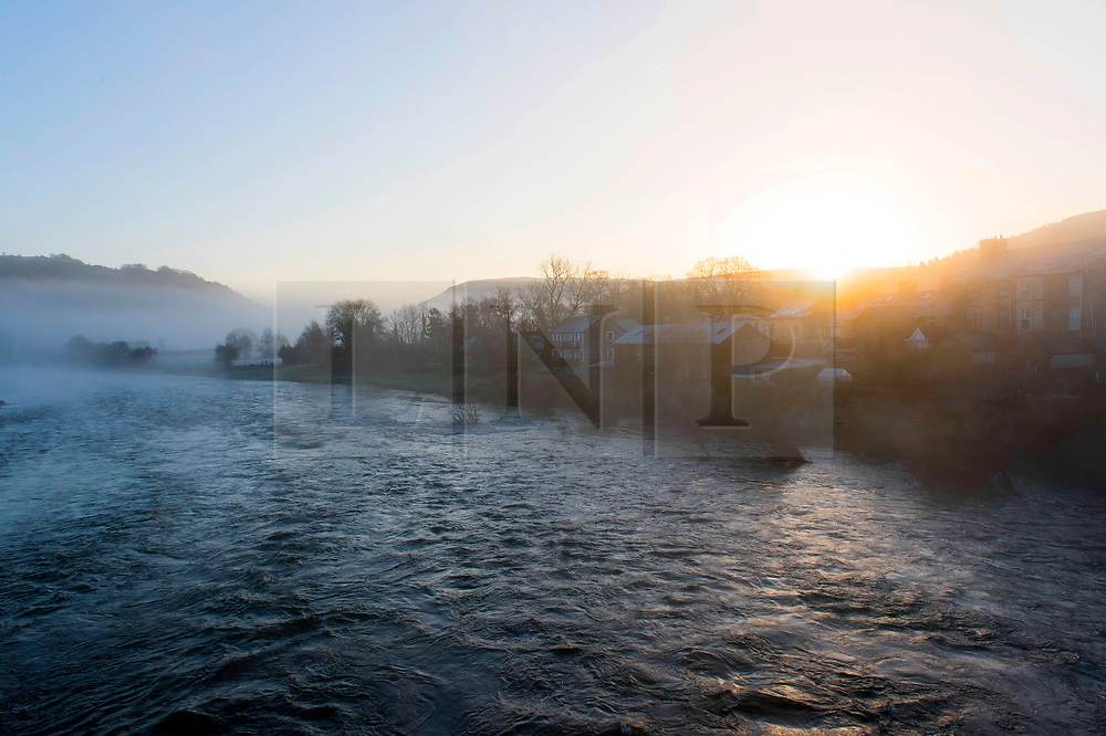 © Licensed to London News Pictures. 16/03/2020. Builth Wells, Powys, Wales, UK. The sun rises over a misty river Wye at Builth Wells in Powys, Wales, UK. after temperatures dropped to below freezing last night. Photo credit: Graham M. Lawrence/LNP