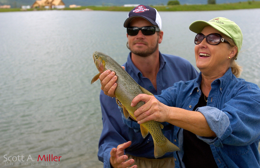 Victor, ID.:  June 8, 2006 - Nancy Cofiell laughs as she takes her catch from Vance Freed of World Cast Anglers while learning to fly fish at Teton Springs in Victor, Idaho...Golfweek/Scott A. Miller