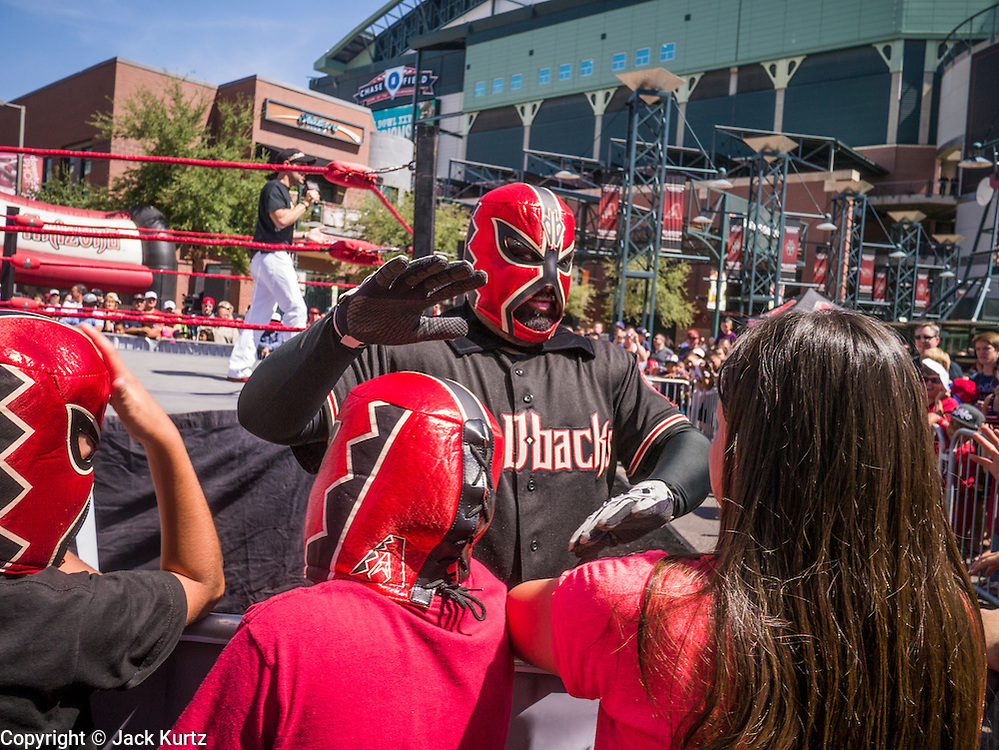 16 SEPTEMBER 2012 - PHOENIX, AZ:  A Lucha Libre wrestler wearing an Arizona Diamondbacks Lucha Libre mask greets fans before a match Sunday. The Arizona Diamondbacks hosted their 14th Annual Hispanic Heritage Day, Sunday to kick off Hispanic Heritage Month (Sept. 15-Oct. 15) before the 1:10 p.m. game between the D-backs and San Francisco Giants. The main attraction of the Day was three Lucha Libre USA exhibition wrestling matches in front of Chase Field stadium before the game.   PHOTO BY JACK KURTZ