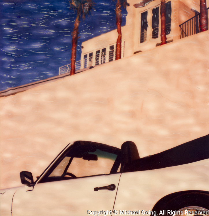 1988 white Porsche Carerra convertible left side profile against sandstone wall with palm trees and blue sky
