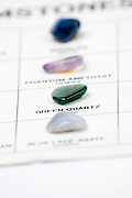 Cutout of a gemstone identification chart on white background Selective focus on Green Quartz