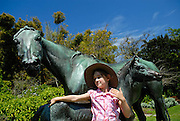 Child (6 years old) playing on bronze mare (La Reyna) and her foal by the French artist, Arthur J. le Duc. Royal Botanic Gardens, Sydney, Australia
