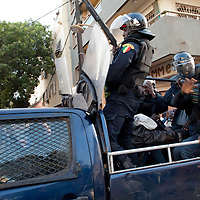 Policeman beats an Anti-government protesters  in central Dakar, Senegal Friday, Feb. 17, 2012. Anti-government protesters and police clashed for a third consecutive day Friday, engaging in running street battles of rock throwing and tear gas in the streets of Dakar's downtown Plateau neighborhood. Demonstrators are defying a government ban on protests to call for the departure of 85-year-old President Abdoulaye Wade, who is running for a third term in next week's election.