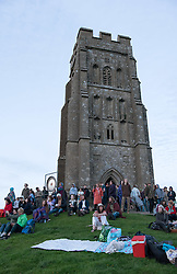 © Licensed to London News Pictures.20/06/2016. Glastonbury, Somerset, UK. Sunset on Glastonbury Tor as people prepare to celebrate the Summer Solstice and the shortest night of the year on top of Glastonbury Tor. This year is a leap year and so the actual Solstice fell on 20 June. There was also a 'Strawberry' full moon to coincide with the Solstice, the first time for decades. Photo credit : Simon Chapman/LNP