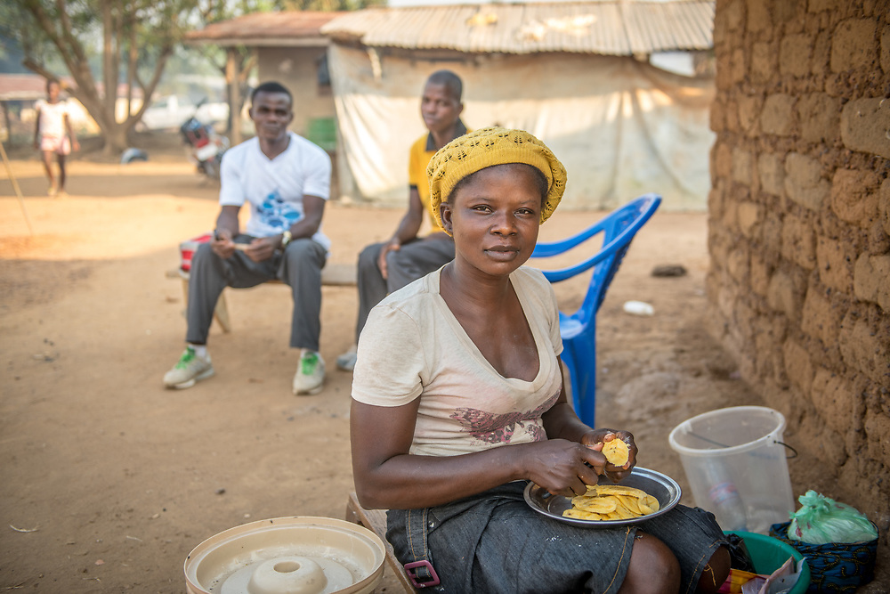 A young woman cuts food for a meal in Ganta, Liberia