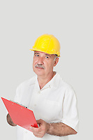 Portrait of senior constructor standing with clipboard over gray background