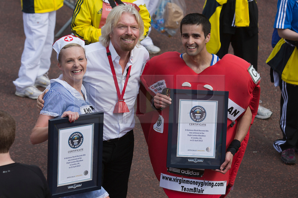© Licensed to London News Pictures. 21/04/2013. London, England. Picture: Sir Richard Branson posese with Runners attempting Guinness World Records. Celebrity Runners and Fun Runners finish the Virgin London Marathon 2013 race in the Mall, London. Many wore black ribbons to pay their respect for those who died or were injured in the Boston Marathon. Photo credit: Bettina Strenske/LNP