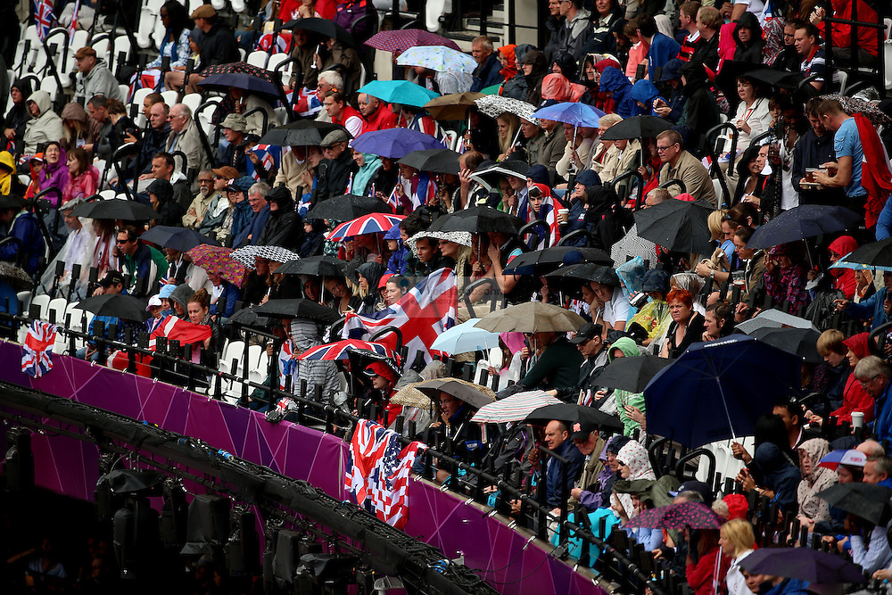 Fans look on in the rain during the track and field event at the Olympic Stadium during day 6 of the London Olympic Games in London, England, United Kingdom on August 3, 2012..(Jed Jacobsohn/for The New York Times)..