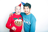 Portrait of a Senior adult man and a young Asian man wearing Christmas jumpers and party hats