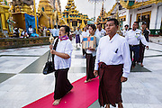 15 JUNE 2013 - YANGON, MYANMAR:   A woman leads a family's merit making procession around Shwedagon Pagoda in Yangon. The Shwedagon Pagoda is officially known as Shwedagon Zedi Daw and is also called the Great Dagon Pagoda or the Golden Pagoda. It is a 99 metres (325 ft) tall pagoda and stupa located in Yangon, Burma. The pagoda lies to the west of on Singuttara Hill, and dominates the skyline of the city. It is the most sacred Buddhist pagoda in Myanmar and contains relics of the past four Buddhas enshrined: the staff of Kakusandha, the water filter of Koṇāgamana, a piece of the robe of Kassapa and eight strands of hair fromGautama, the historical Buddha. The pagoda was built between the 6th and 10th centuries by the Mon people, who used to dominate the area around what is now Yangon (Rangoon). The pagoda has been renovated numerous times through the centuries. Millions of Burmese and tens of thousands of tourists visit the pagoda every year, which is the most visited site in Yangon.   PHOTO BY JACK KURTZ