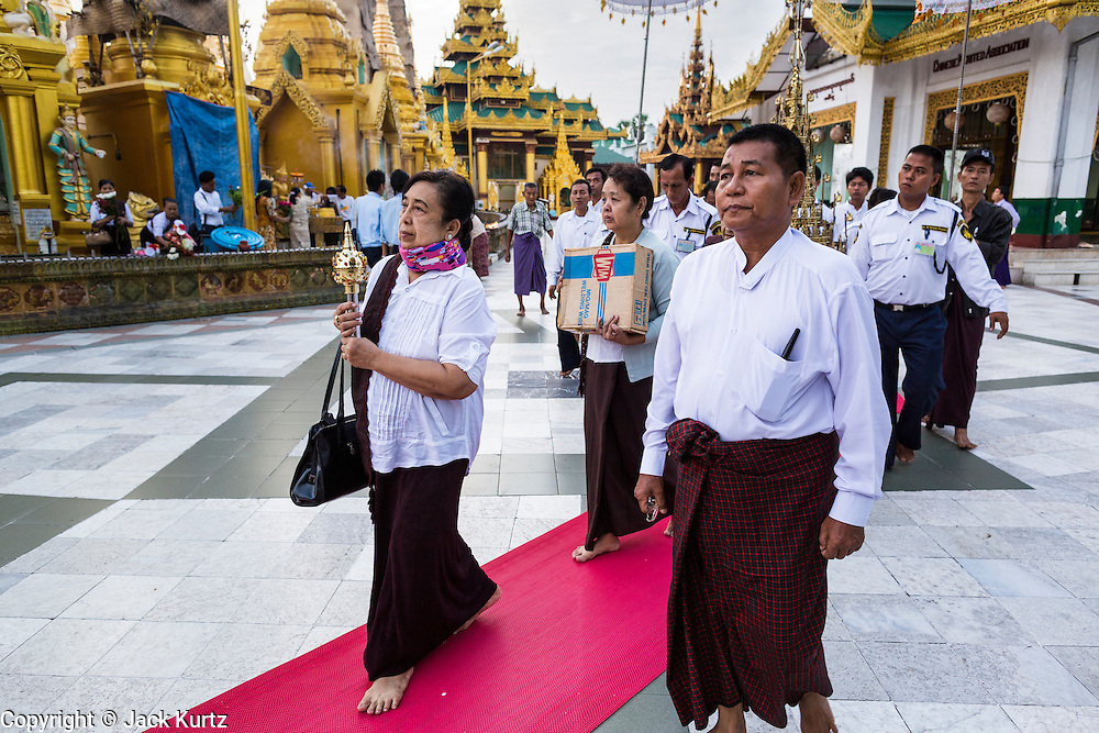 15 JUNE 2013 - YANGON, MYANMAR:   A woman leads a family's merit making procession around Shwedagon Pagoda in Yangon. The Shwedagon Pagoda is officially known as Shwedagon Zedi Daw and is also called the Great Dagon Pagoda or the Golden Pagoda. It is a 99 metres (325ft) tall pagoda and stupa located in Yangon, Burma. The pagoda lies to the west of on Singuttara Hill, and dominates the skyline of the city. It is the most sacred Buddhist pagoda in Myanmar and contains relics of the past four Buddhas enshrined: the staff of Kakusandha, the water filter of Koṇāgamana, a piece of the robe of Kassapa and eight strands of hair fromGautama, the historical Buddha. The pagoda was built between the 6th and 10th centuries by the Mon people, who used to dominate the area around what is now Yangon (Rangoon). The pagoda has been renovated numerous times through the centuries. Millions of Burmese and tens of thousands of tourists visit the pagoda every year, which is the most visited site in Yangon.   PHOTO BY JACK KURTZ