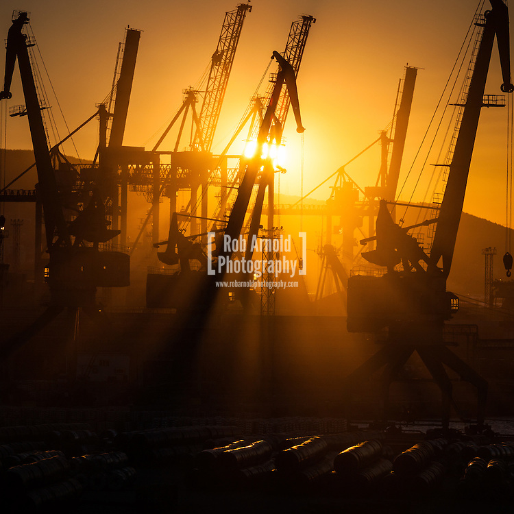 Sunrise breaks through cranes on the quay in the Black Sea port of Novorossiysk.