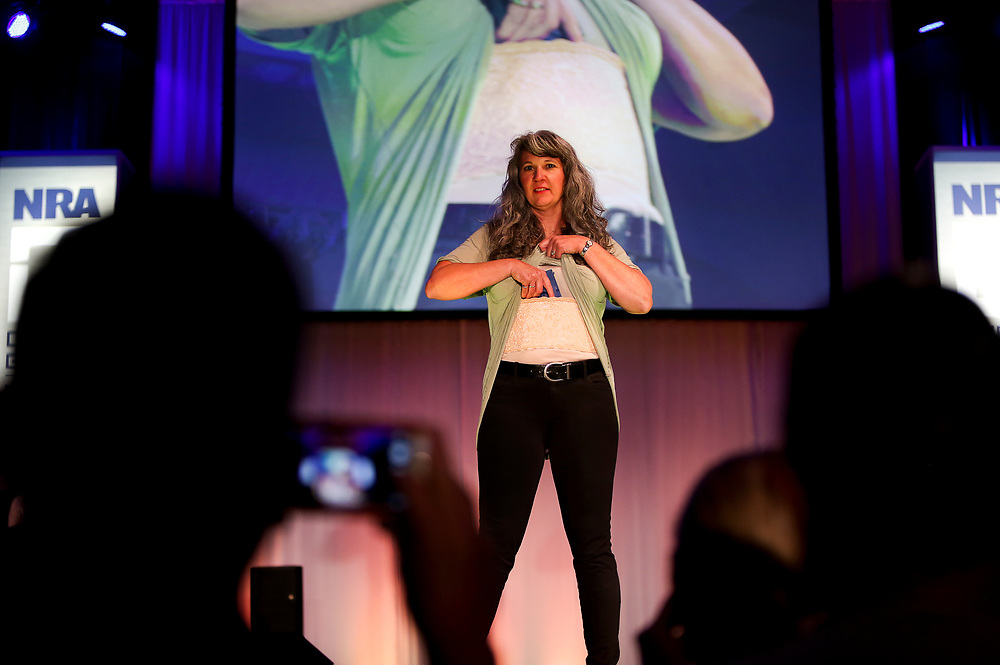 A model displays the use of a concealed torso holster during the National Rifle Association (NRA) Carry Guard Expo Fashion Show in Milwaukee, Wisconsin, U.S., August 25, 2017.   REUTERS/Ben Brewer