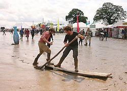 © Licensed to London News Pictures. 24/06/2012. Somerset, UK. Two men use a piece of wood as a raft across the mud. Festival goers enjoy the mud and the sunshine at The Sunrise Festival held at Bruton In Somerset today 24 June 2012. Photo credit : Jason Bryant/LNP