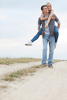 Young man piggybacking woman on trail at field