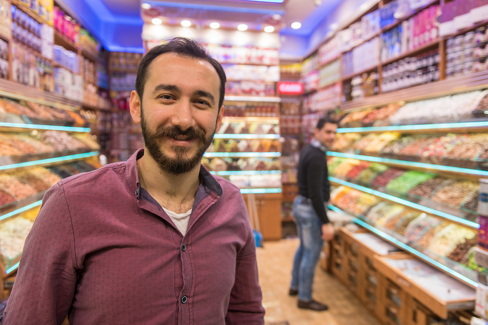 Adult male merchant smiles and poses for photo in his sweets and dried goods shop, Istanbul Spice bazaar in Turkey