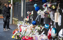 © Licensed to London News Pictures. 28/01/2018. London, UK. A young couple look at floral tributes at the scene where three teenage pedestrians were killed near a bus stop in Hayes, West London after a black Audi collided with them. Named locally as Harry Rice, Josh Kennedy and George Wilkinson, the three teenagers were hit on Friday night  close to the M4 Junction 4. A 28-year-old man has been arrested and a police are currently looking for a  second man believed to have been in the Audi.. Photo credit: Ben Cawthra/LNP