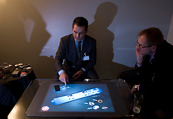 """A Microsoft representative demonstrates a $10,000 coffee table PC, the Surface. It features touchscreen technology that can sense and process multiple touches at the same time and """"turns an ordinary tabletop into a vibrant interactive surface."""" It's intended for enhancing customer experiences inside retail stores -- or perhaps creating some really cool bar games. At the moment the Surface is available only to select partners in the United States, although Microsoft was gauging a possible entry into the European market. (Photo © Jock Fistick)"""
