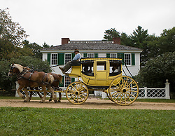 A horse drawn stagecoach carries visitors past the Salem Town House, Old Sturbridge Village (OSV), a re-created New England town of the 1830s, is a living history museum in Sturbridge, Massachusetts.  OSV, the largest living museum in New England, stands on 200 acres on farm land that once belonged to David Wight.