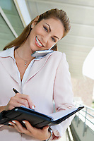 Businesswoman writing in planner while using cell phone outdoors, portrait