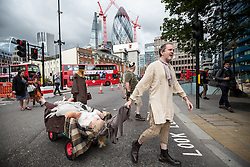 © Licensed to London News Pictures. 04/09/2015. London, UK. Actors in traditional costumes take part in a procession from Minories (near the Tower of London) to St Botolph without Aldgate Church in which they dragged a cart with 'plague victims' and yelled 'bring out your dead' to passing members of public. This is to mark 350 years since the plague pit at church was completed. It also marks the opening of the Great Plague Festival which runs until September 6th. Photo credit : James Gourley/LNP