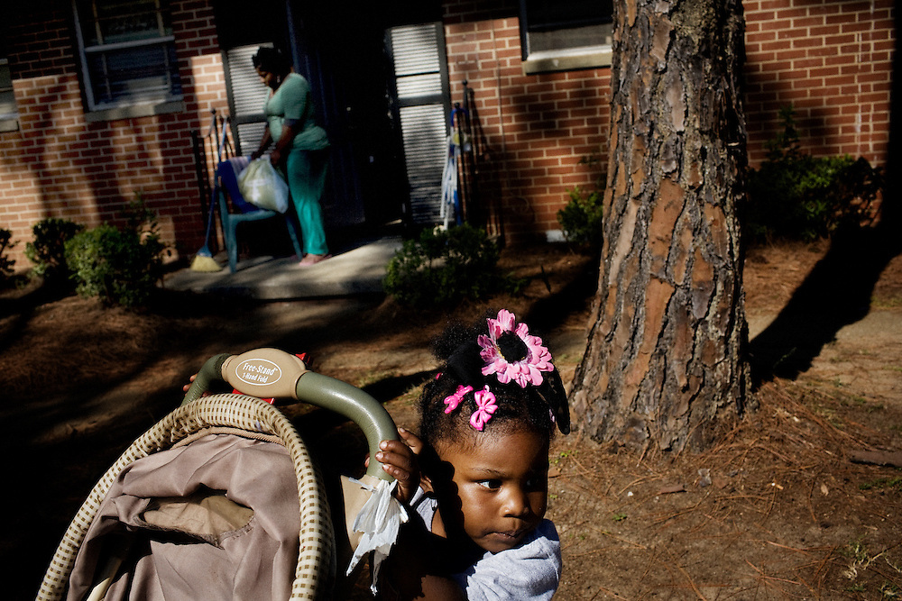 """Gabby, 2, plays with a stroller outside the apartment she shares with her mother, Lettorea """"Lottie"""" Clark, 25, in Albany, GA on Wednesday, October 22, 2008. Lottie and Gabby live off welfare after escaping an abusive relationship with Gabby's father."""