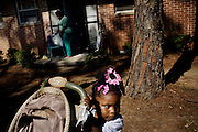 "Gabby, 2, plays with a stroller outside the apartment she shares with her mother, Lettorea ""Lottie"" Clark, 25, in Albany, GA on Wednesday, October 22, 2008. Lottie and Gabby live off welfare after escaping an abusive relationship with Gabby's father."