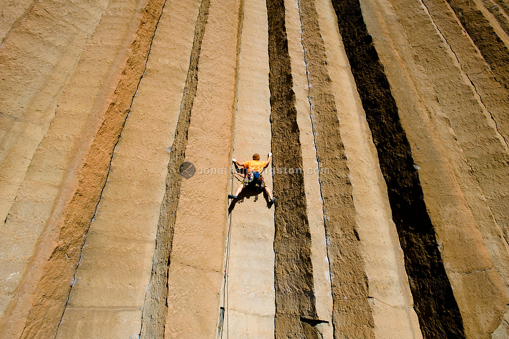A mid adult man rock climbing a crack at Trout Creek, Oregon. (Model Released)