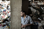 Egypt, Cairo: Nouar, 28 years old, stands inside the place where he works. Nouar is a garbage collector. He collects Cairo's trash and recycle it inside Moqattam, the christian coptic quarter in Cairo where live 40.000 Zabbaleen (garbage collectors). ph.Christian Minelli.