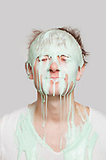 Paint dripping down a young Caucasian man's face against gray background
