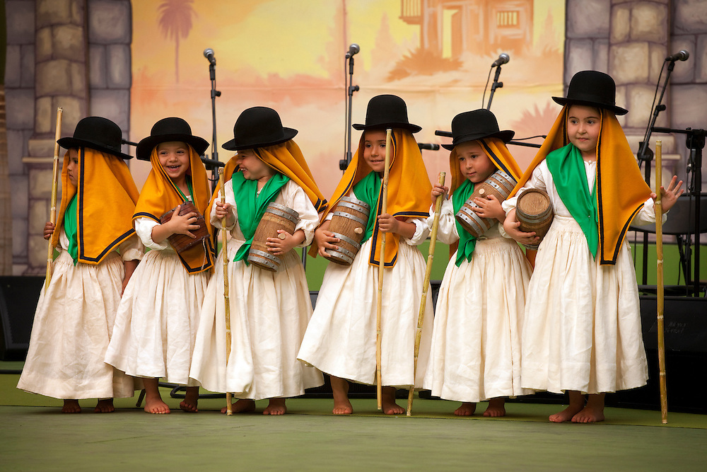 A group of giggling girls. Traditional costumes competition for kids in island capital Santa Cruz, Tenerife.