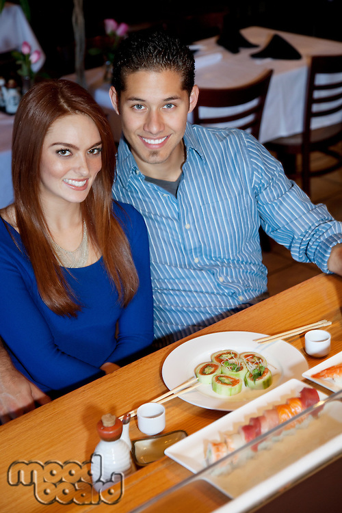 Portrait of a happy young couple in Japanese restaurant eating sushi