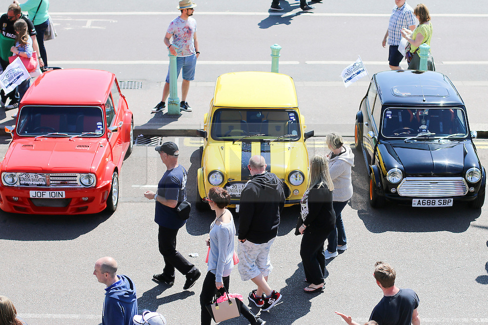 © Licensed to London News Pictures. 17/05/2015. Brighton, UK. Member of the public walk past mini cars on the seafront at Brighton which are taking part in the London to Brighton Mini Run. Photo credit : Hugo Michiels/LNP