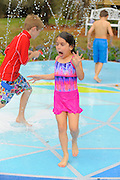 Homeowners John and Ileana Trautwein's six-year-old daughter Victoria tries out the family's new Mickey Mouse shaped splash pad. The family's yard was transformed with an EPCOT theme. As seen on HGTV's My Yard Goes Disney.