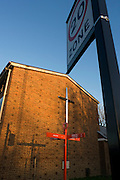 The cross on the wall of Herne Hill's United Reform Church and the direction sign post (and its shadow) of Red Post Hill.