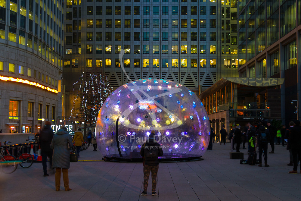 Canary Wharf, London, January 16 2018. Commuters walk past 'Come closer', a six-metre wide living, breathing installation that pulsates with light and sound when you approach or touch it, emitting a warm glow through 236 programmed LEDs as it constantly generates new visual patterns to a unique soundtrack, created by Australian firm Eness, at the Winter Lights festival at Canary Wharf in London which features over 30 spectacular light installations at interactive art. © Paul Davey