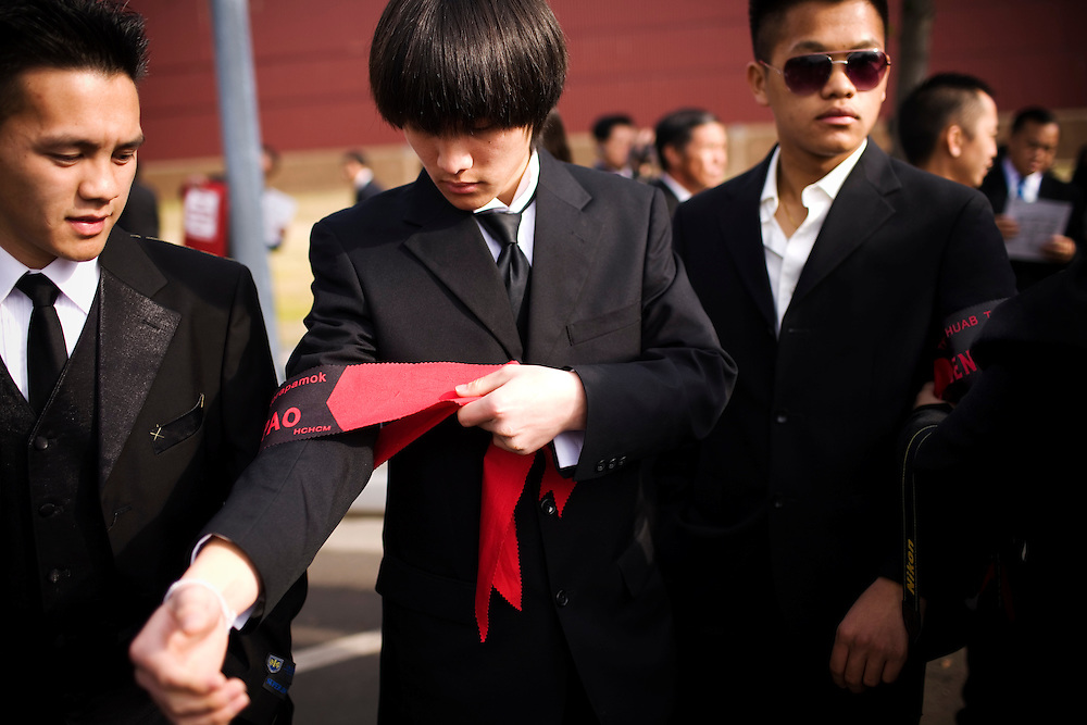 Kingsley Yang, with his brothers, ties an arm band during the funeral procession for General Vang Pao, the start of a six-day-long funeral, in Fresno, Ca., on Friday, Feb. 4, 2011. Thousands from the Hmong community, former CIA and military officers mourn the loss of the general who led Hmong guerrillas in a CIA-backed battle against communist forces in Laos and helped tens of thousands of Hmong resettle in American cities.