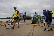 Cyclists disembarking and boarding the small chain ferry crossing the River Yare in Reedham on the Norfolk Broads.