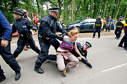 © London News Pictures. 19/08/2013. Balcombe, UK. A young female activist is wrestled to the ground and detained by police as activists clash with police outside the Cuadrilla drilling site in Balcombe, West Sussex on a day of of civil disobedience organised by campaign group No Dash For Gas. Cuadrilla has temporarily ceased drilling at the site, which has been earmarked for fracking, under advice from the police. Photo credit: Ben Cawthra/LNP