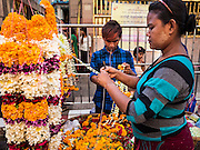 "22 OCTOBER 2015 - YANGON, MYANMAR: Flower garland sellers near the entrance of Sri Kali temple in Yangon on the last day of Navratri. Navratri, literally ""nine nights"" is a Hindu festival devoted to the Goddess Durga. Navratri festival combines ritualistic puja (prayer) and fasting. Navratri in India follows the lunar calendar and is celebrated in September/October as Sharad Navratri. It's widely celebrated in countries in Southeast Asia that have large Hindu communities, including Myanmar (Burma). Many of Myanmar's Hindus are descendants of Indian civil servants and laborers who came to Myanmar when it was the British colony of Burma.   PHOTO BY JACK KURTZ"