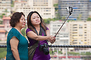 MONACO, MONACO - JUNE 17, 2015: Unidentified asian women make selfie with a smartphone on a stick at the viewpoint in Monaco.