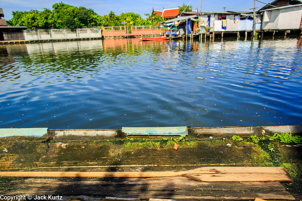 03 JANUARY 2013 - BANGKOK, THAILAND:  An empty canoe in Phra Khanong canal near Wat Mahabut. Just a few minutes from downtown Bangkok, the neighborhoods around Wat Mahabut interlaced with canals, still resemble the Bangkok of 60 years ago. Wat Mahabut is a large temple off Sukhumvit Soi 77. The temple is the site of many shrines to Thai ghosts. Many fortune tellers also work on the temple's grounds.   PHOTO BY JACK KURTZ