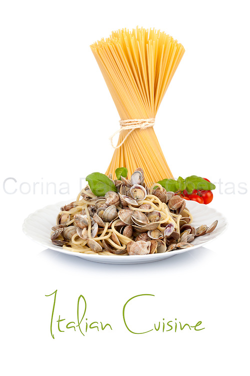 Spaghetti with lupins clams, traditionally Italian plate. In the background raw sapaghetti, basil leaves and cherry tomatoes.