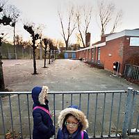 Nederland, Amsterdam , 21 november 2014.<br /> De Evangelische basisschool Tanisha in Amsterdam moet dicht.<br /> Twee basisscholen moeten op 1 januari dicht vanwege de slechte onderwijskwaliteit. Het gaat om de basisscholen Tanisha in Amsterdam en nevenvestiging Talitha in Utrecht, allebei van de Christelijke Evangelische Vereniging voor Ouders (CEVO). Dat hebben de scholen vandaag gehoord van staatssecretaris Sander Dekker (Onderwijs)<br /> Op de foto: kinderen wachten vanmorgen voor de school totdat de deur opengaat.<br /> Foto:Jean-Pierre Jans
