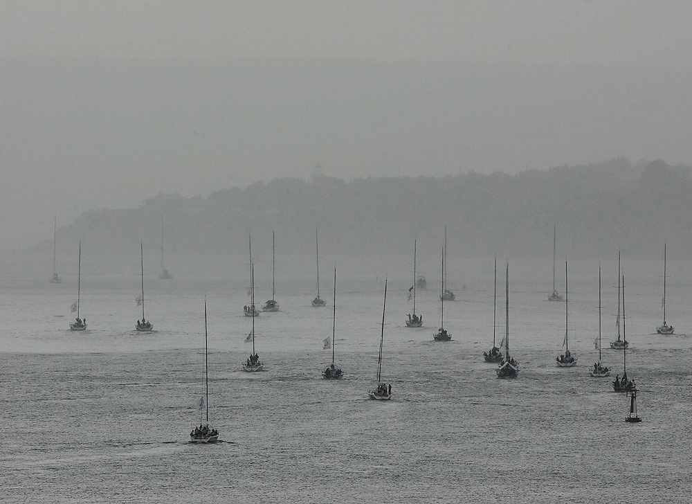 The Farr 40 world championship fleet make their way up Sydney Harbour during a morning shower.