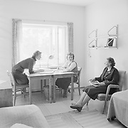 Two female students at boarding school in a dormitory room with adult woman housemistress teacher, Helsinki, Finland, 1950s